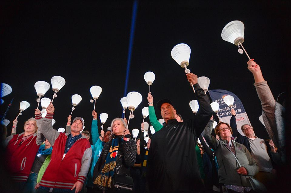 Image of participants standing with arms up holding small lit lanterns in the night