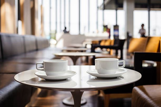 Image of a coffee shop blurred and focus on a small white table with two white coffee cups