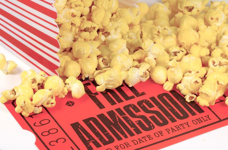 "Close up photo of popcorn falling out of a container onto a ""free admission"" red movie ticket"