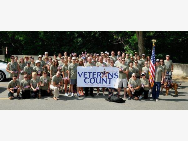"Photo of veterans in a parking lot holding an American flag and a sign that says ""Veterans Count&"