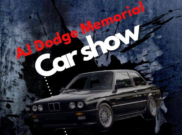 Picture of a black car driving out of a dark wall, with the event name in red and white text
