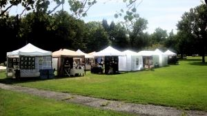Photo of art show featuring white tents on a slightly-wooded grass lawn