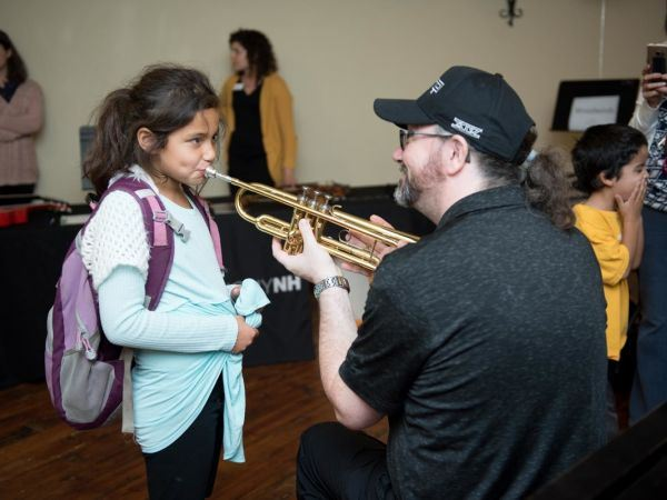 Photo of a teacher holding a trumpet for a young girl learning to play