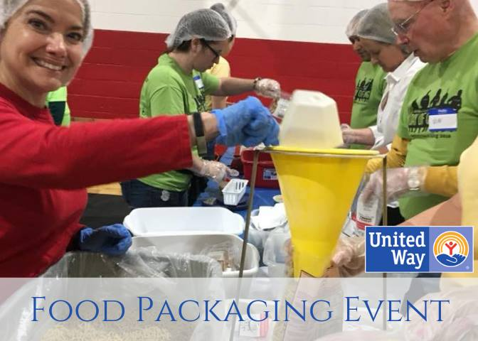 Image of volunteers in hair nets and blue gloves packaging food