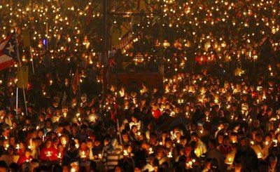 Image of crowd of people holding lit candles at night