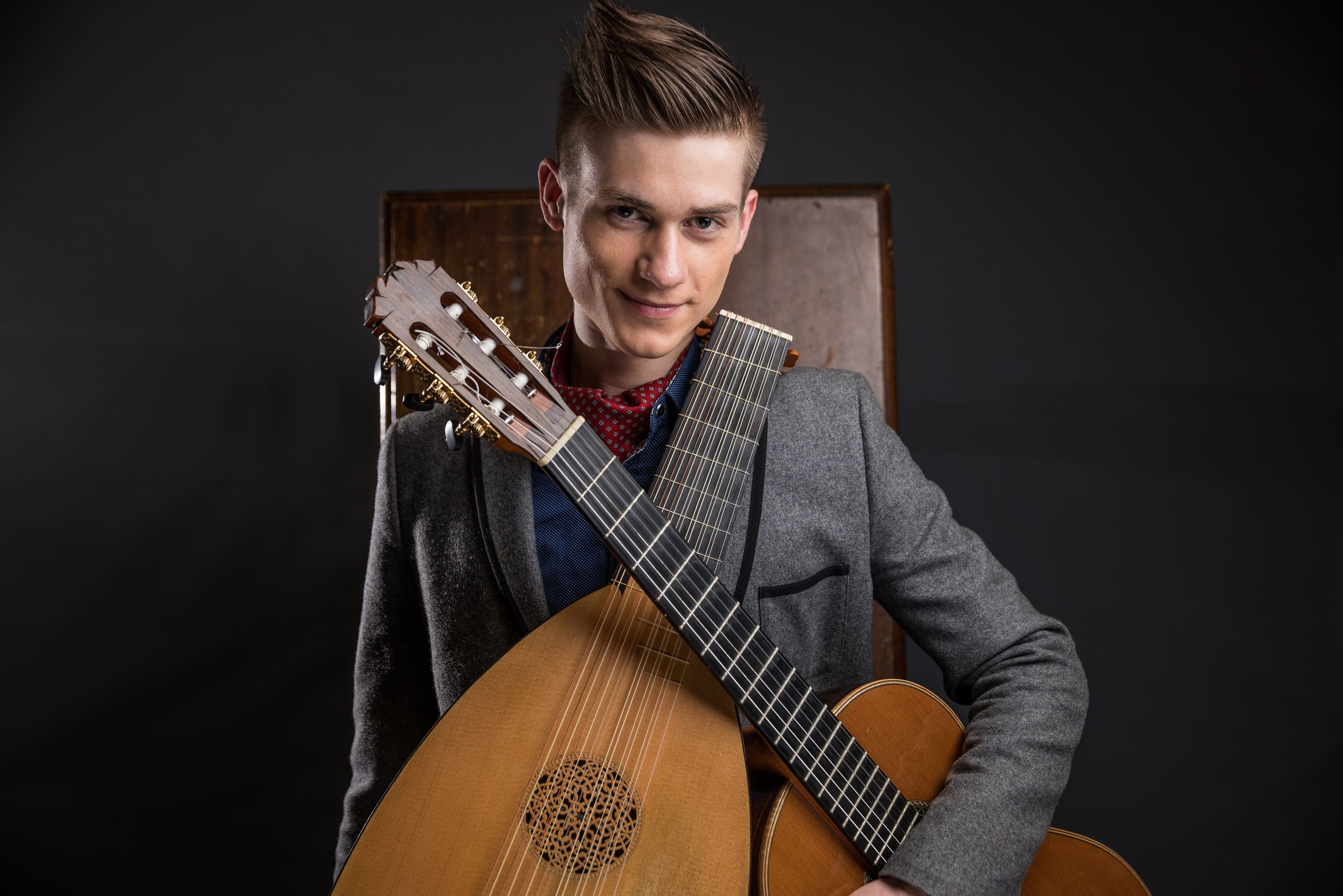 Image of musician in a grey suit holding 2 lutes