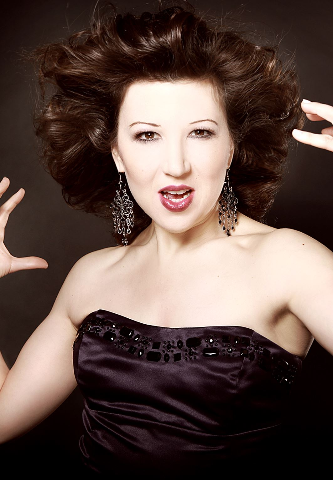 Image of singer in a black strapless gown in front of a black background