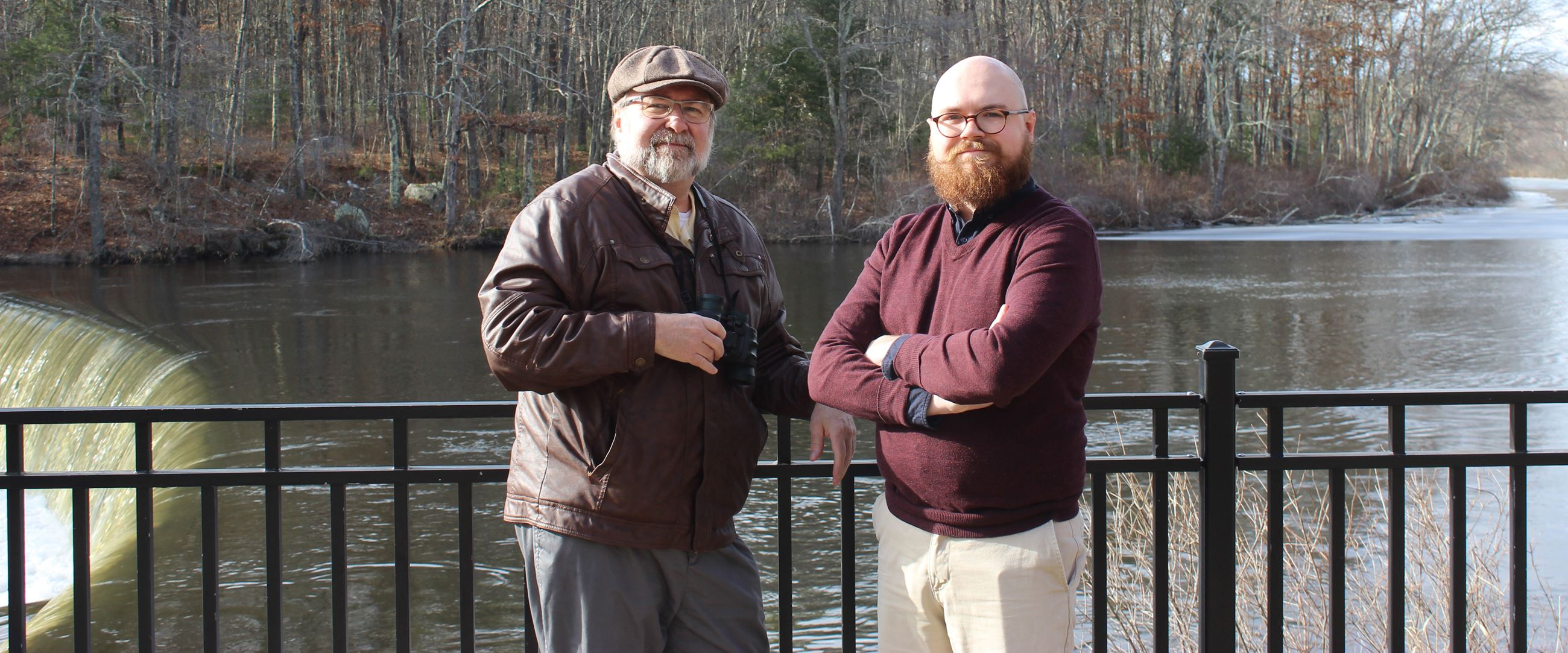 Photo of two men standing in front of a black railing, pond or river in the background