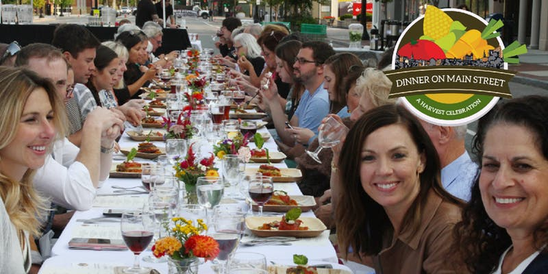 Image of people enjoying dinner at a communal table from past event