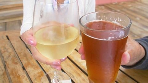 Image of hands holding a beer and a glass of white wine