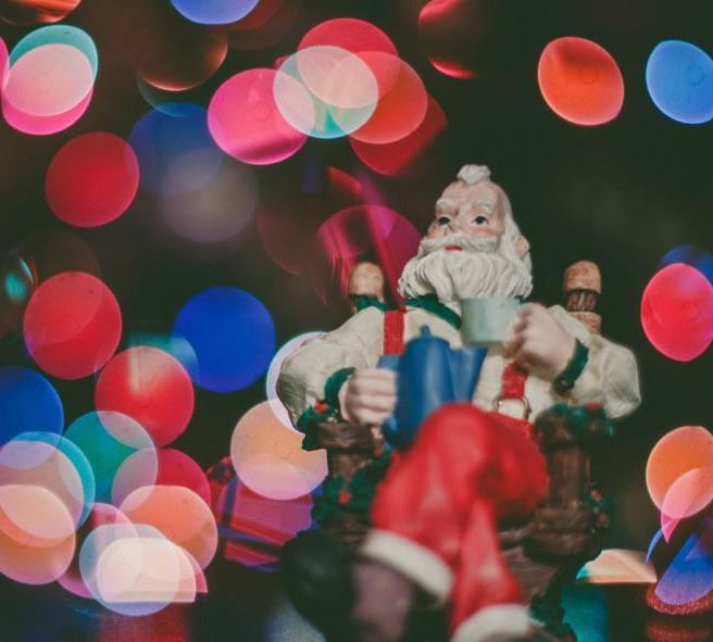 Image of Santa figurine sitting in a chair surrounded by Christmas lights