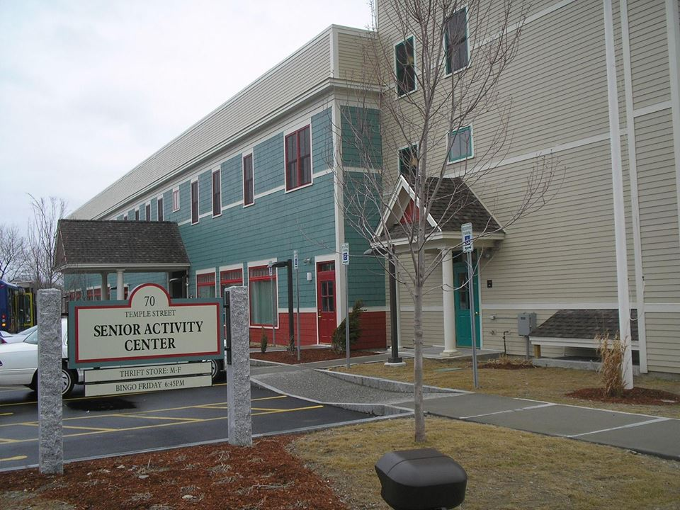 Image of the outside of the senior center, a teal and red building next to a tan building
