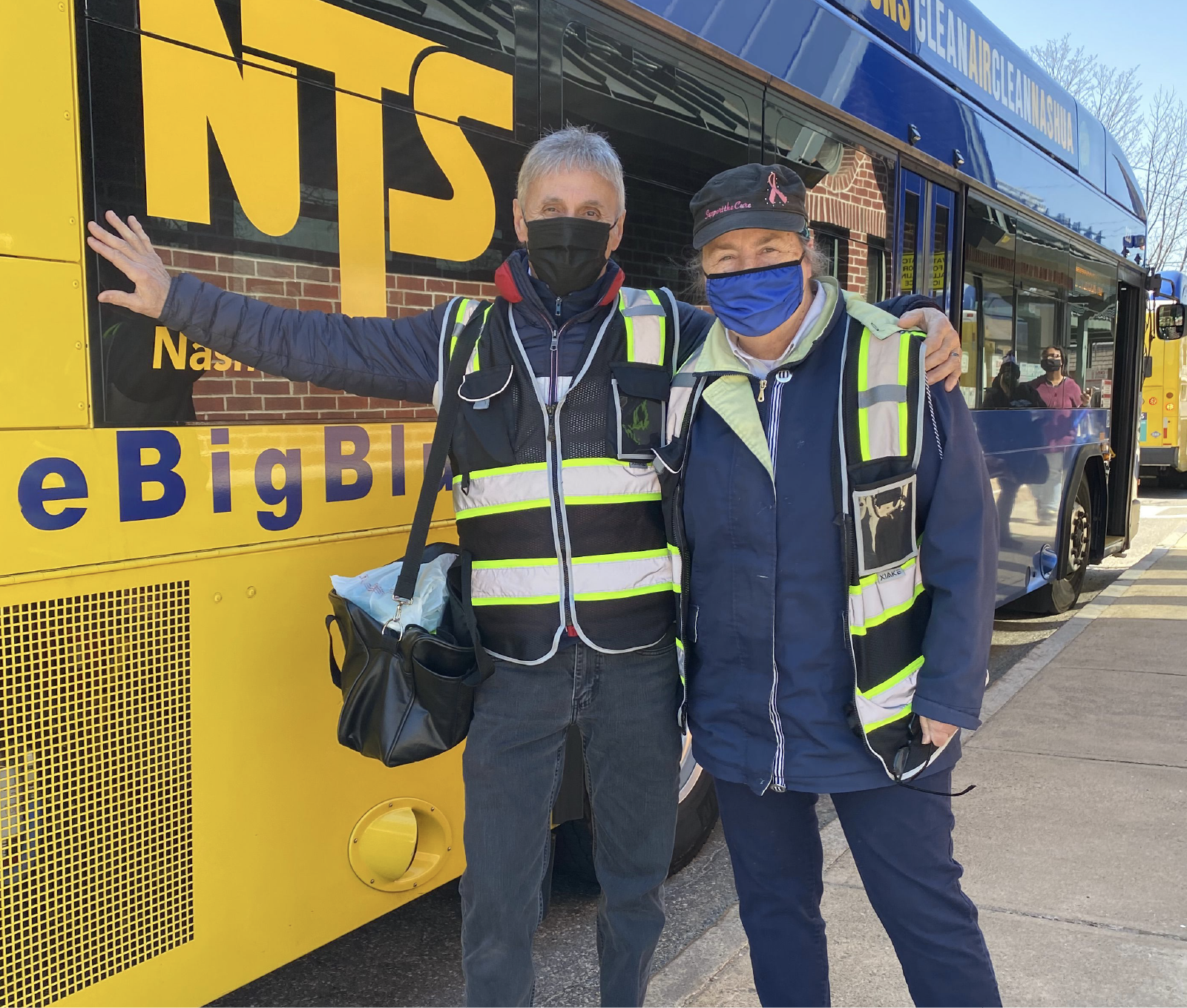 Two drivers stand in front of an NTS bus