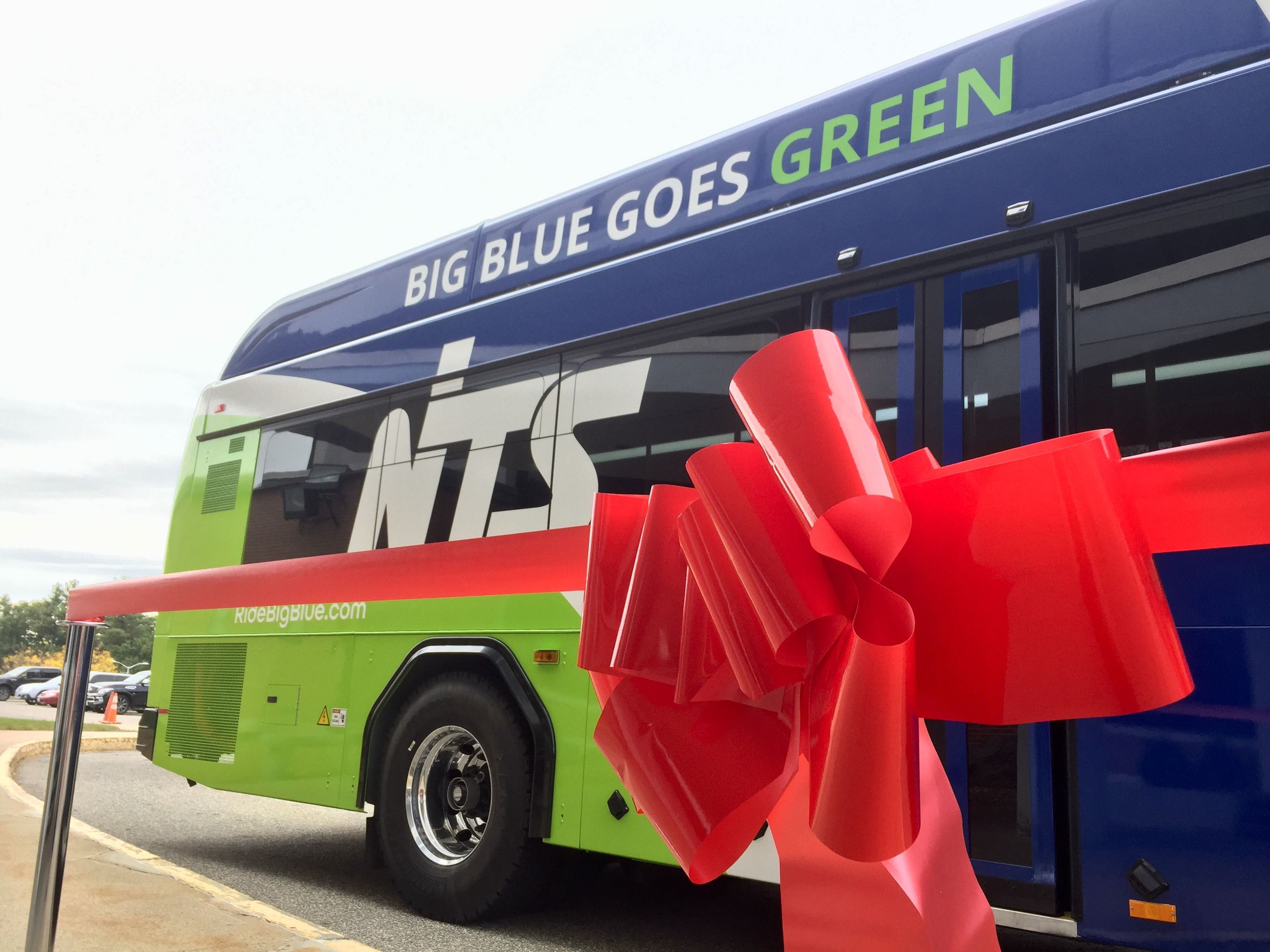 A giant red ribbon sits in front of Nashua Transit Systems new blue and lime green electric hybrid b