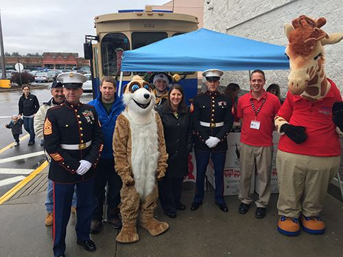 Volunteers, officers, and mascots take a group photo by the Toys for Tots table