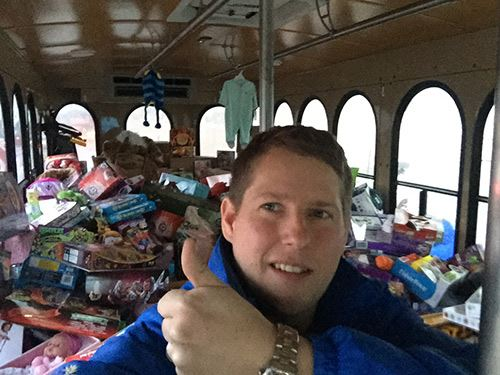 A man gives a thumbs up as he stands in front of a pile of donated toys