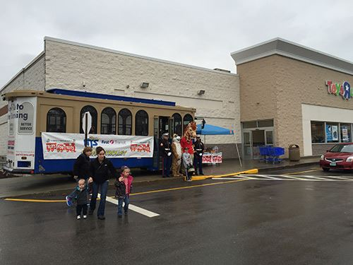 A booth and trolley sit outside of Toys R' Us for the Toys for Tots drive