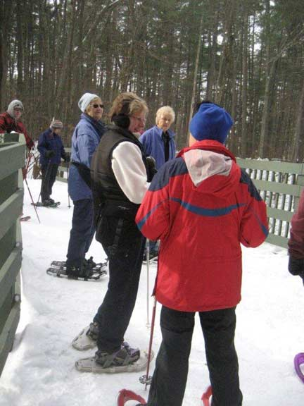 Group of people in snowshoes chatting together.