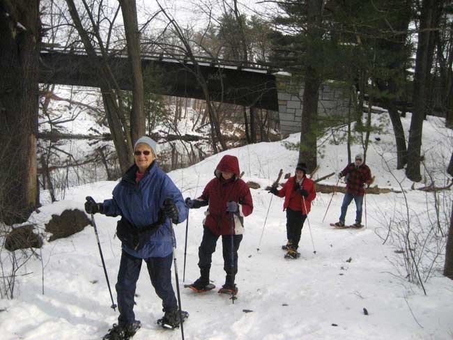 Group walking in snowshoes up a hill.