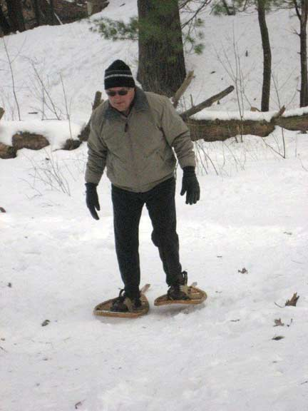 Man learning to walk in snowshoes.