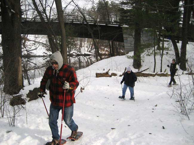 Two people hiking up a hill in snowshoes.