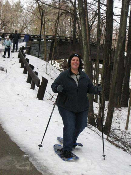 Woman in snowshoes smiling on a path.