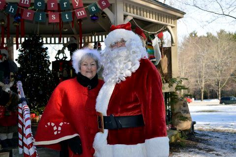 Santa and Mrs. Claus standing in front of gazebo.