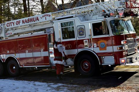 Santa waving next to a fire truck.