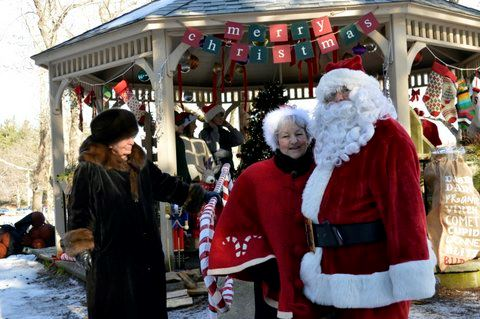 Woman greeting Santa and Mrs. Claus.