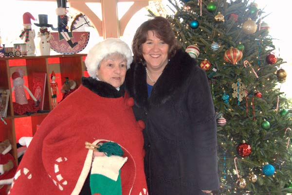 Woman standing with Mrs. Claus.