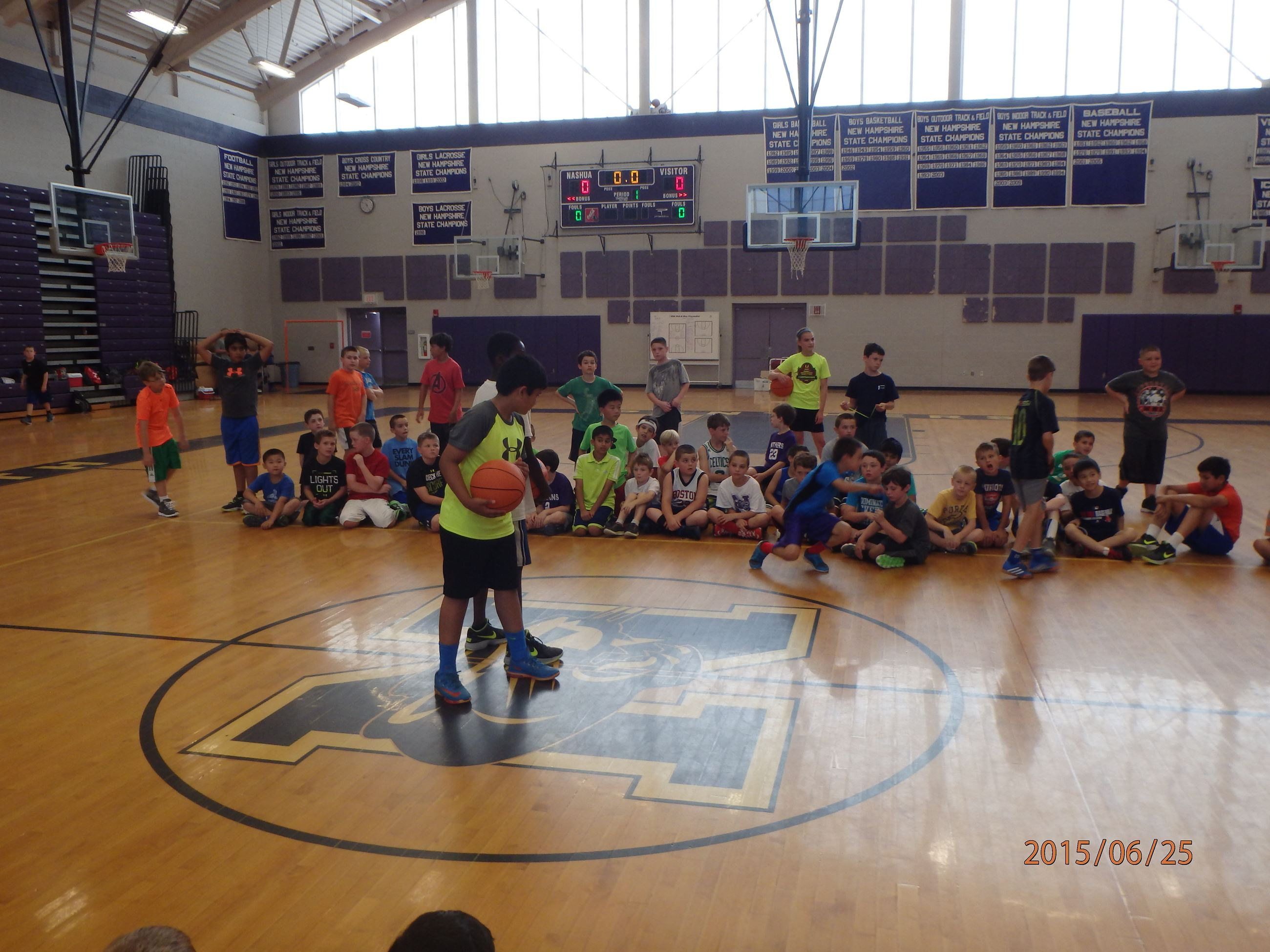 Boys gathered in a gym for basketball camp.