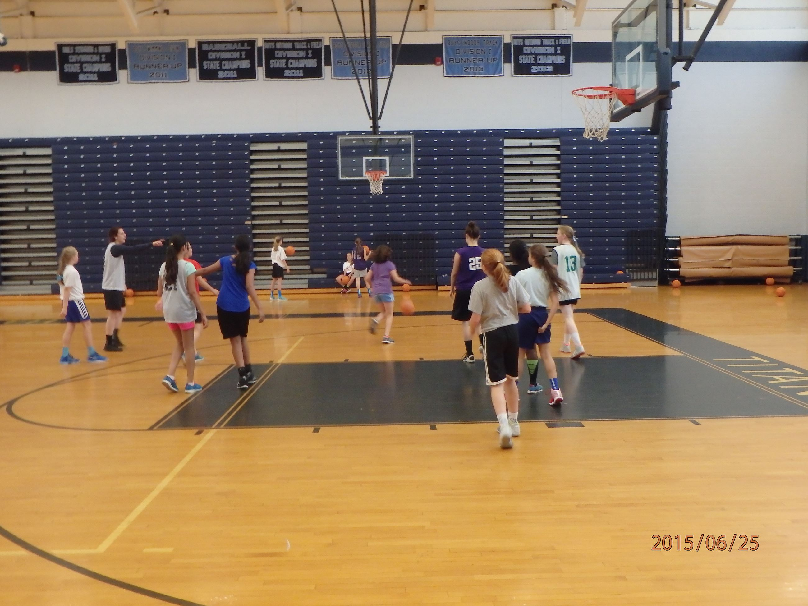 Girls gathered in a gym for basketball camp.