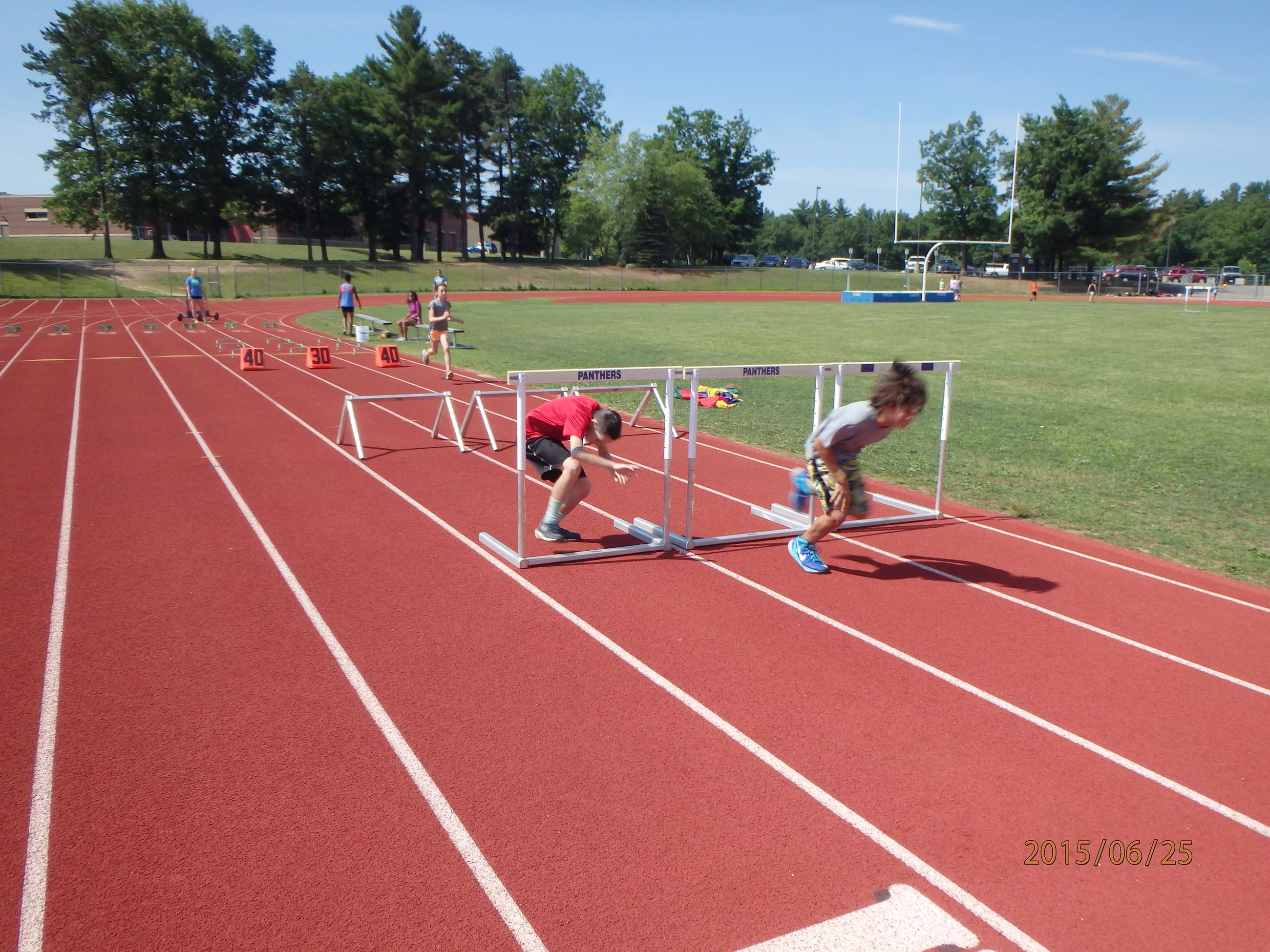 Track and Field Camp runners practicing hurdles.